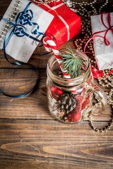 Рождество, х mason jar с елочными украшениями, еловыми шишками, искусственным снегом, леденцом и еловой веткой. на деревянном столе.