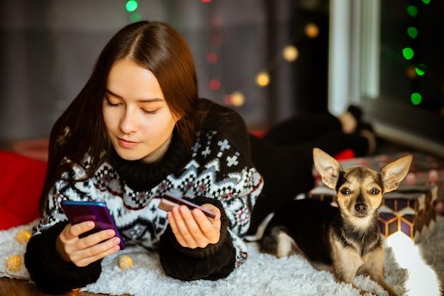 겨울 스웨터를 입은 젊은 여성이 구매하는 크리스마스 안전한 온라인 쇼핑