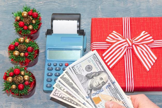クリスマスセール。リボン付きの赤いギフトボックスとコーン付きの小さなクリスマスツリーの近くのレジの上にドルを持っている手。オンラインショッピング。正月とクリスマスのプレゼントを買う