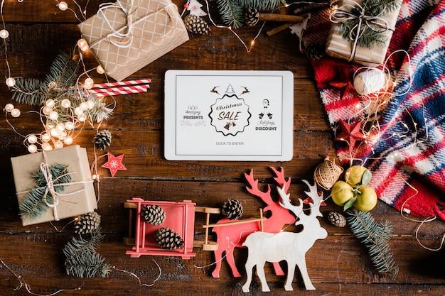 Объявление о рождественской распродаже на тачпаде в окружении традиционных украшений и символов на деревянном столе