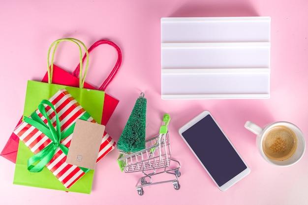 クリスマスセールブラックフライデーの背景女の子の手持ちのシンボル新年セール-ショッピングバッグ、ギフトボックス、ショッピングカート、銀行カード、スマートフォン、ピンクのカラフルな背景上面図