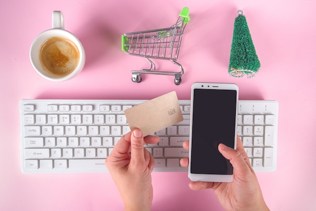 クリスマスセールブラックフライデーの背景とショッピング赤緑の紙袋、ショッピングカート、銀行カード、コンピューターのキーボード、女の子の手にスマートフォントップビューフラットレイ