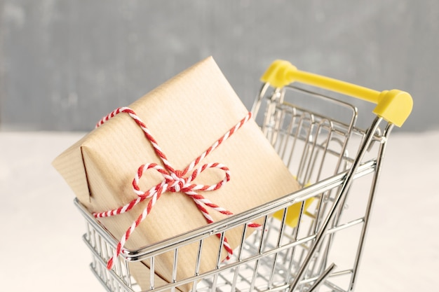 Christmas sale concept - gift with craft paper and red and white twisted cord in small shopping cart.