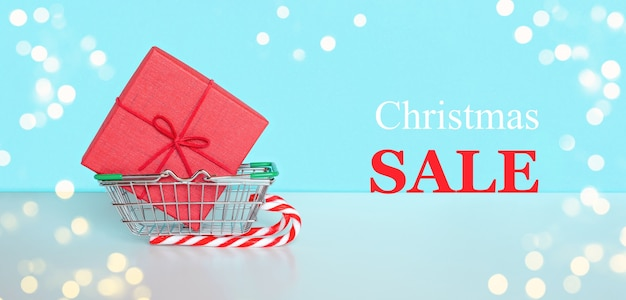 ショップカートとギフトショッピングトロリーギフトボックス付きのクリスマスセールメッセージテキストクリスマスセール