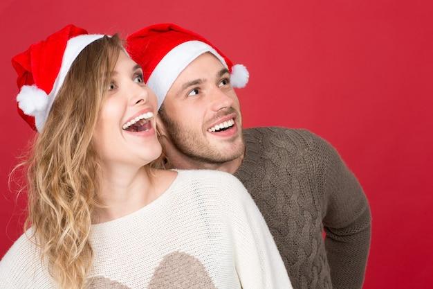 Рождественские распродажи идут! веселая молодая зимняя пара взволнованно смотрит на copyspace сбоку на красном