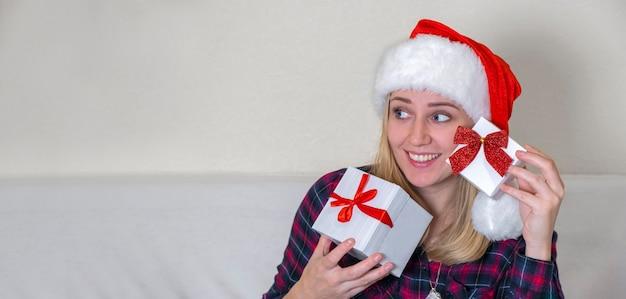 クリスマスセール。顔の前にクリスマスプレゼントボックスを保持している幸せな若い女性