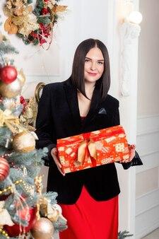 크리스마스 산타입니다. 아름 다운 웃는 여자 모델입니다. 조립. 녹색 크리스마스 트리 근처 아름 다운 행복 한 젊은 여자. 성인 여성
