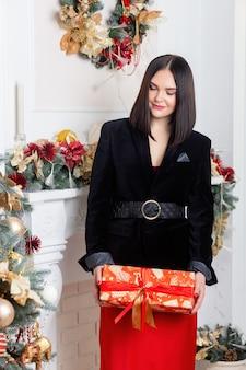 크리스마스 산타입니다. 아름 다운 웃는 여자 모델입니다. 조립. 크리스마스 트리 조명 배경 위에 빨간 치마와 검은 재킷에 우아한 아가씨. 새해 복 많이 받으세요. 손에 선물