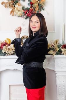 크리스마스 산타입니다. 아름 다운 웃는 여자 모델입니다. 조립. 크리스마스 트리 조명 배경 위에 빨간 치마와 검은 재킷에 우아한 아가씨. 새해 복 많이 받으세요.