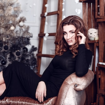 Christmas santa. beautiful smiling woman model. makeup. healthy long hair style. elegant lady in black dress over christmas tree lights background. happy new year