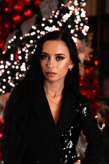 クリスマスサンタ美しい笑顔の女性モデルメイク健康的な長い髪のスタイル赤いドレスのエレガントな女性