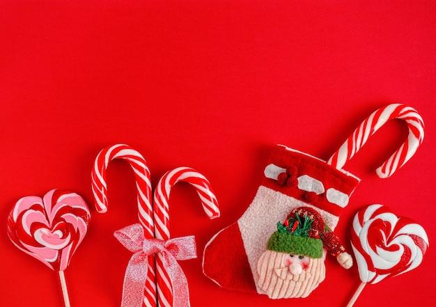 赤い背景の上のキャンディーとクリスマスサンタブーツ
