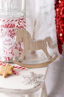 Шляпа санта-клауса рождества висит на деревянном стуле, концепции xmas, украшения над деревянными предпосылкой grunge.