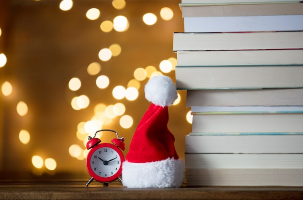 Christmas santa claus hat and pile of books