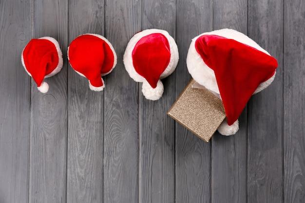 나무 배경에 가족을 위한 크리스마스 산타 클로스 모자