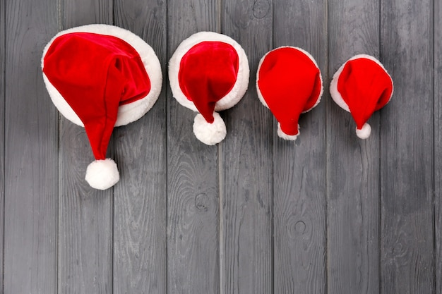 木製の背景に家族のためのクリスマスサンタクロースの帽子