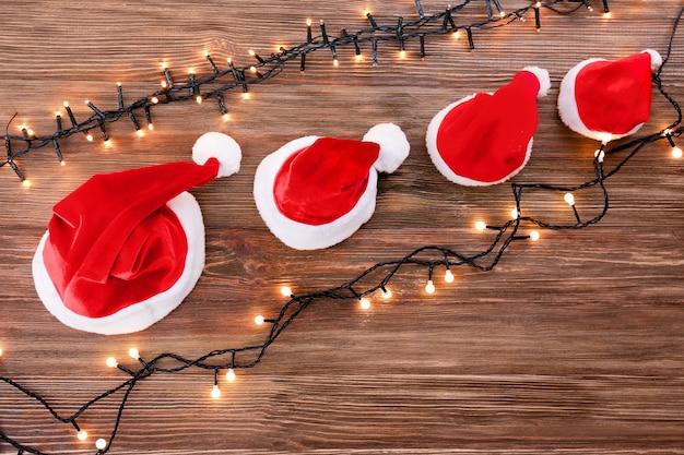 나무 배경에 화환이 있는 가족을 위한 크리스마스 산타클로스 모자