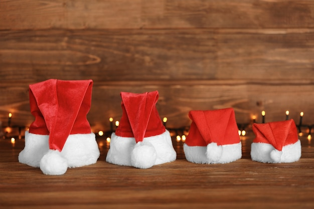木製のテーブルに花輪を持つ家族のためのクリスマスサンタクロースの帽子