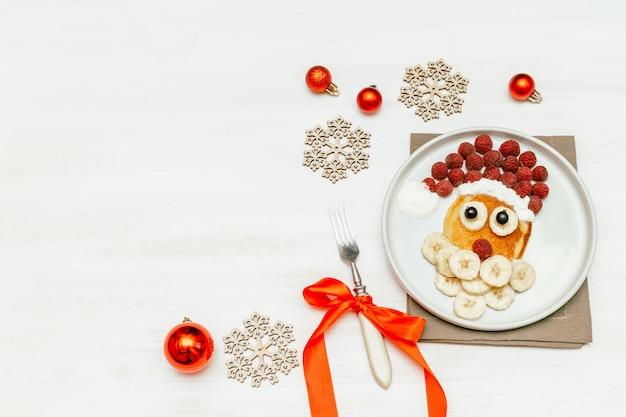 크리스마스 산타 클로스 모양의 팬케이크 달콤한 신선한 라즈베리 베리와 바나나 어린이 어린이 아침 식사에 대 한 접시 흰색 나무 배경. 복사 공간이 있는 새해 장식이 있는 크리스마스 음식.