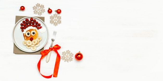 크리스마스 산타 클로스 모양의 팬케이크 달콤한 신선한 라즈베리 베리와 바나나 접시 흰색 나무에