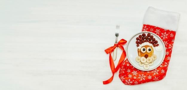 크리스마스 산타클로스 모양의 팬케이크는 달콤한 신선한 라즈베리 베리와 바나나를 흰색 나무 배경에 접시에 올려 아이들의 아침 식사를 제공합니다. 복사 공간 배너와 함께 크리스마스 음식 새 해 장식입니다.