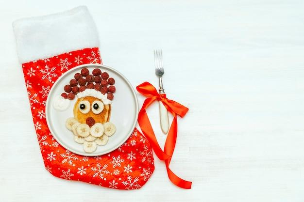 크리스마스 산타클로스 모양의 팬케이크는 달콤한 신선한 라즈베리 베리와 바나나를 흰색 나무 배경에 접시에 올려 아이들의 아침 식사를 제공합니다. 복사 공간이 있는 크리스마스 음식 새해 장식.
