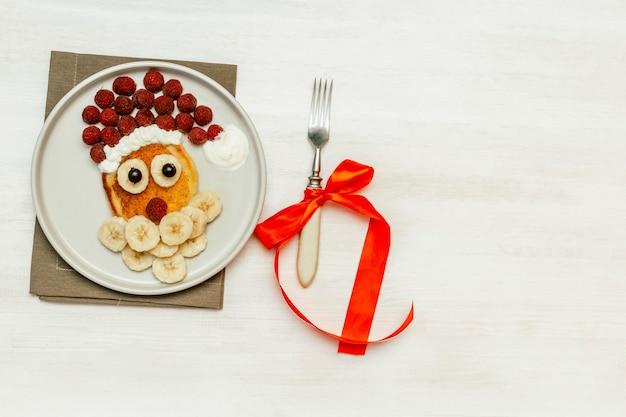 크리스마스 산타클로스 모양의 팬케이크는 달콤한 신선한 라즈베리 베리와 바나나를 흰색 나무 배경에 접시에 올려 아이들의 아침 식사를 제공합니다. 복사 공간이 있는 새해 장식이 있는 크리스마스 음식
