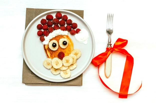 크리스마스 산타클로스 모양의 팬케이크는 달콤한 신선한 라즈베리 베리와 바나나를 흰색 나무 배경에 접시에 올려 아이들의 아침 식사를 제공합니다. 복사 공간이 있는 새해 장식이 있는 크리스마스 음식.