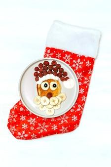 크리스마스 산타클로스 모양의 팬케이크는 달콤한 신선한 라즈베리 베리와 바나나를 흰색 나무 배경에 접시에 올려 아이들의 아침 식사를 제공합니다. 새 해 장식으로 크리스마스 음식입니다.