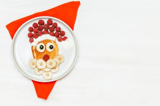 흰색 접시에 달콤한 신선한 라즈베리 베리와 바나나를 곁들인 크리스마스 산타클로스 모양의 팬케이크