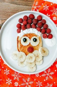 크리스마스 산타클로스 모양의 팬케이크는 달콤한 신선한 라즈베리 베리와 바나나를 나무 배경에 접시에 올려 아이들의 아침 식사를 제공합니다. 새 해 장식으로 크리스마스 음식을 닫습니다.