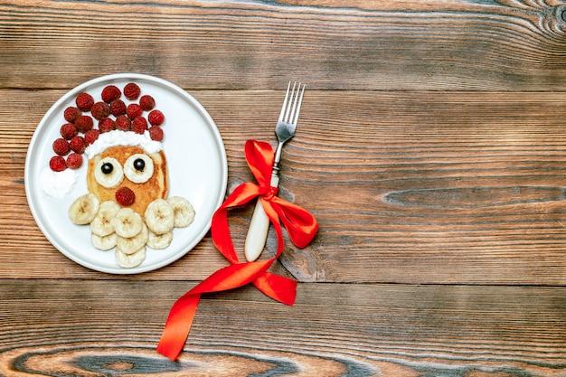 크리스마스 산타클로스 모양의 팬케이크는 달콤한 신선한 라즈베리 베리와 바나나를 나무 배경에 접시에 올려 아이들의 아침 식사를 제공합니다. 복사 공간이 있는 새해 장식이 있는 크리스마스 음식.