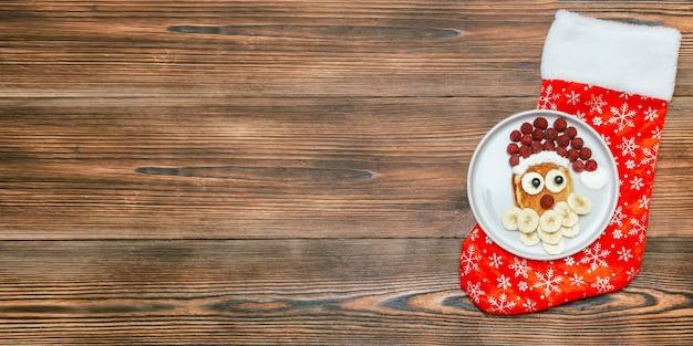 나무에 접시에 달콤한 신선한 라즈베리 베리와 바나나와 크리스마스 산타 클로스 모양의 팬케이크