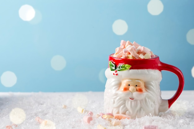 Christmas santa cup of hot chocolate with marshmallow on blue. christmas food and drink concept