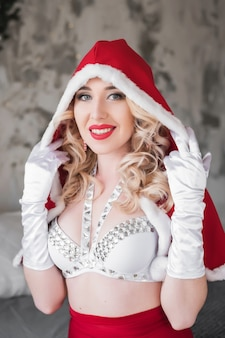 クリスマスサンタの女の子赤と白のスーツの美しい笑顔モデル