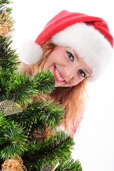 장식된 전나무 뒤에 크리스마스 산타 소녀 얼굴.