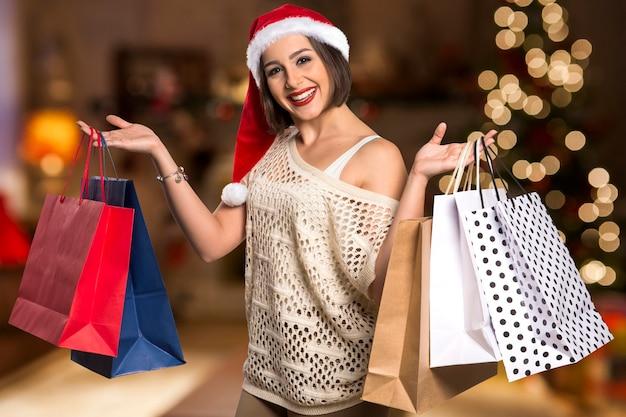 Рождество санта шляпа изолировала женский портрет владением рождественский подарок. улыбающаяся счастливая девушка на фоне рождества