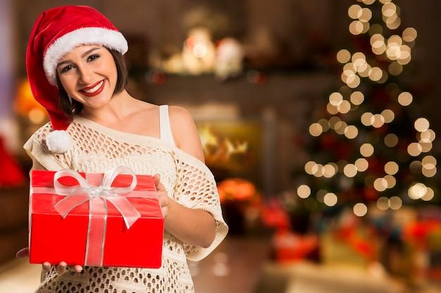 Рождество санта шляпа изолировала женский портрет владением рождественский подарок. улыбается счастливая женщина над рождественскими огнями боке