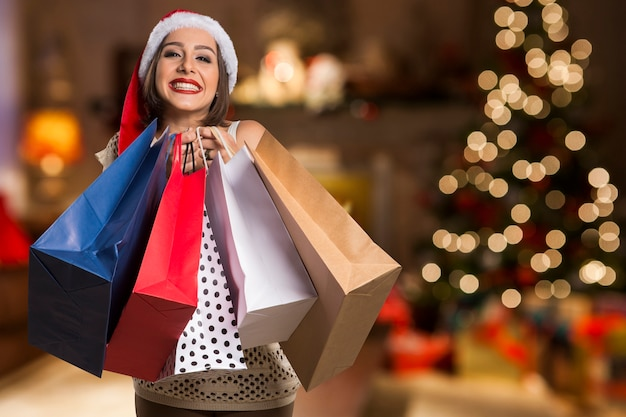 Christmas santa hat isolated woman portrait hold shopping bags. smiling happy woman over bokeh christmas lights