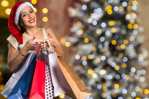 Christmas santa hat isolated woman portrait hold shopping bags. smiling happy woman over christmas bokeh lights