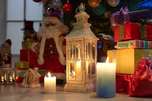 ランタン、キャンドル、ギフトのクリスマスシーン。クリスマスプレゼントやデコレーションをクローズアップ。メリークリスマス、そしてハッピーニューイヤー。冬の休日のお祝い。