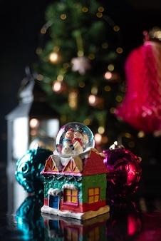 나무, 조명, 스노우 글로브와 함께 크리스마스 장면. 선택적 초점