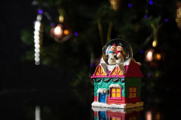 Christmas scene with tree, lights and snow globe. selective focus