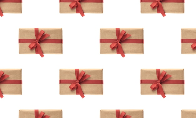 크리스마스 완벽 한 패턴입니다. giftbox 흰색 배경에 고립 된 빨간 리본으로 공예 종이에 싸여 있습니다. 크리스마스, 겨울, 새 해 축 하 개념입니다. 평평한 평지, 평면도, 복사 공간