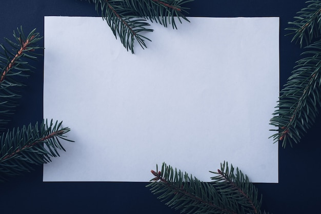 Christmas seasonal background with central blank white card and pine branches forming a border over midnight blue with copyspace for a holiday greeting