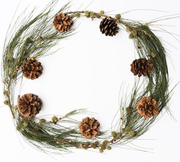 クリスマスの季節の松ぼっくりと白い背景に、フラットレイアウトの新鮮な緑の枝フレーム