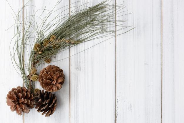 クリスマスの季節の松ぼっくりと白い木製の背景、フラットレイアウトの新鮮な緑の枝フレーム