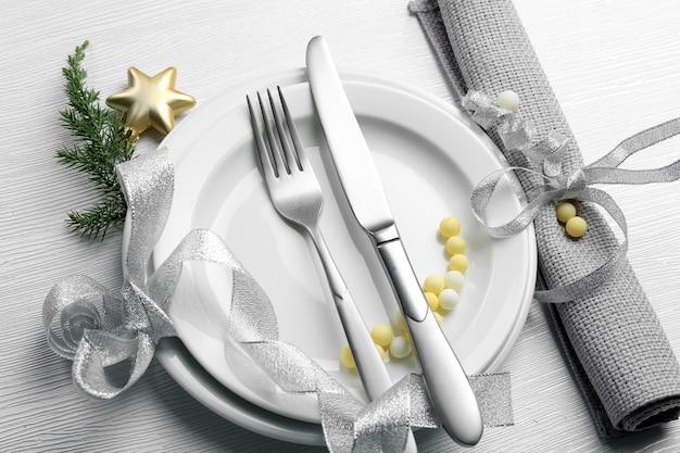 밝은 나무 테이블 위에 접시와 냅킨에 칼 붙이를 제공하는 크리스마스, 닫습니다