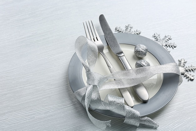 Christmas serving cutlery on plate over light wooden table, close up