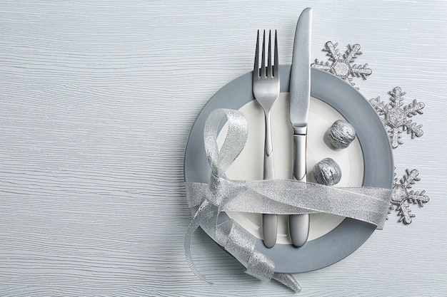 Christmas serving cutlery on plate over light wooden table